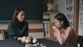 Eun-hee sits with her teacher in the critically acclaimed film HOUSE OF HUMMINGBIRD