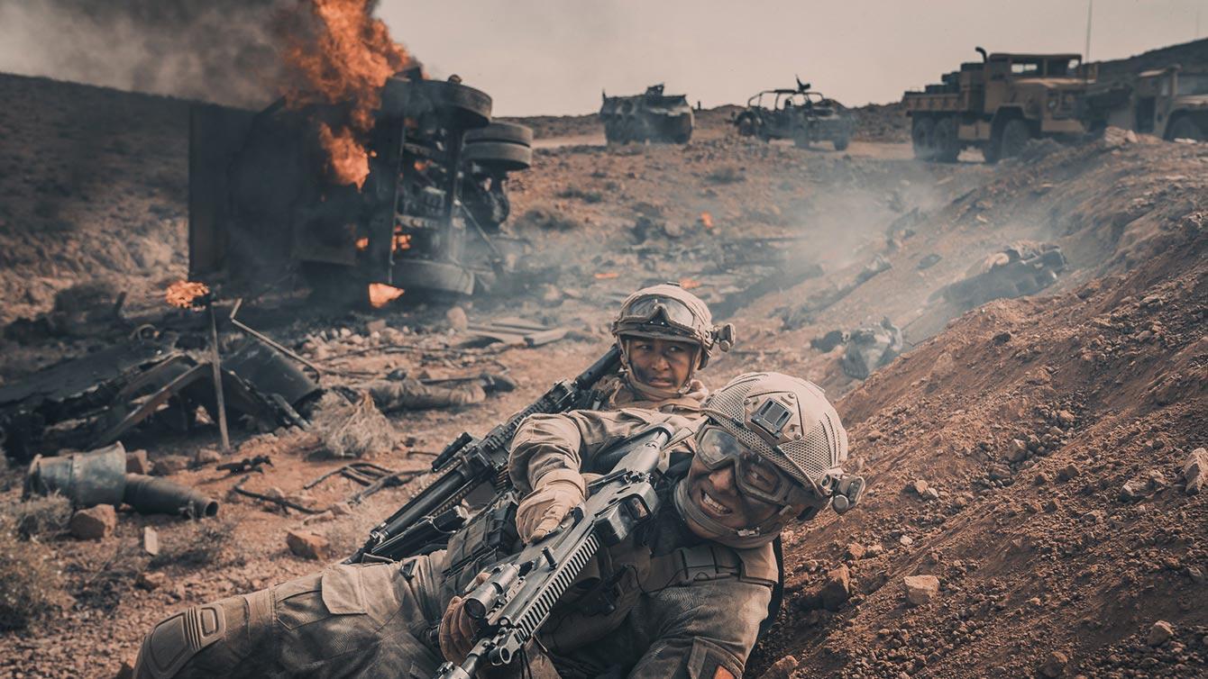 Two soldiers crawl on hillside for cover in OPERATION RED SEA war movie by Well Go USA