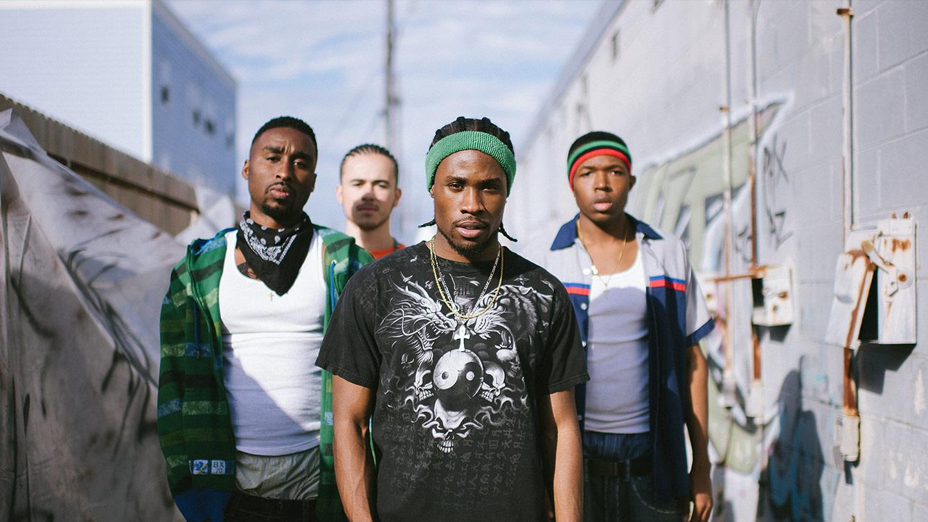 Four young men walk through graffiti streets of New Orleans, Louisiana