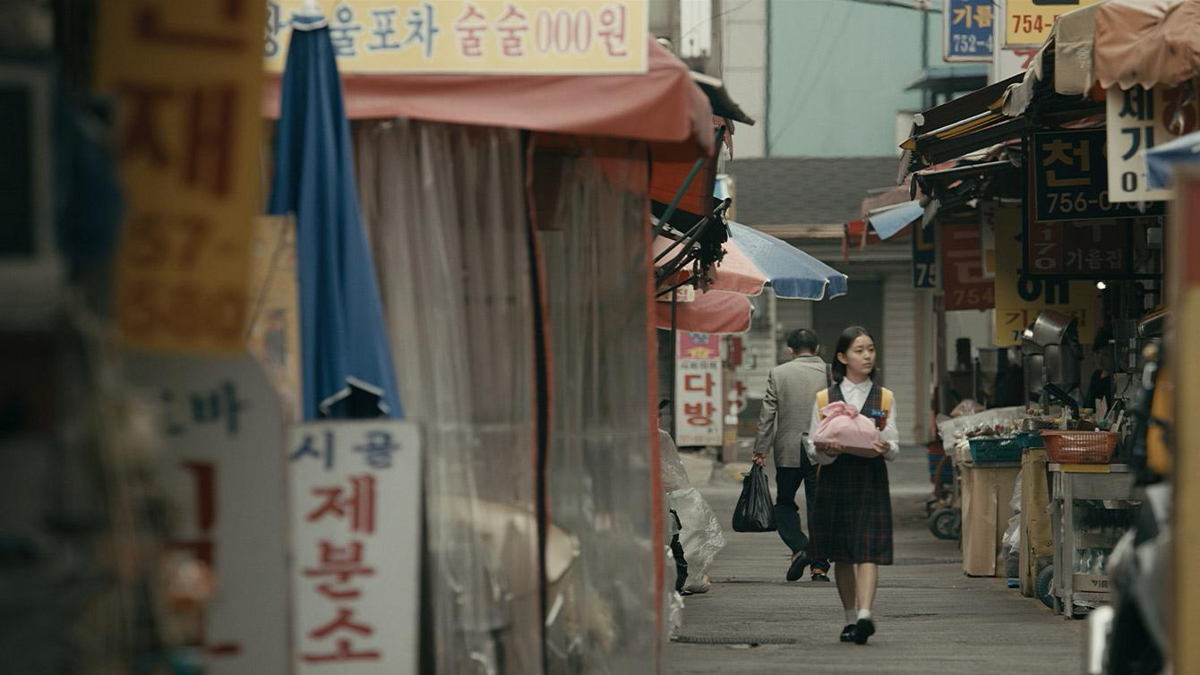Young adolescent Korean girl walks through streets of small town