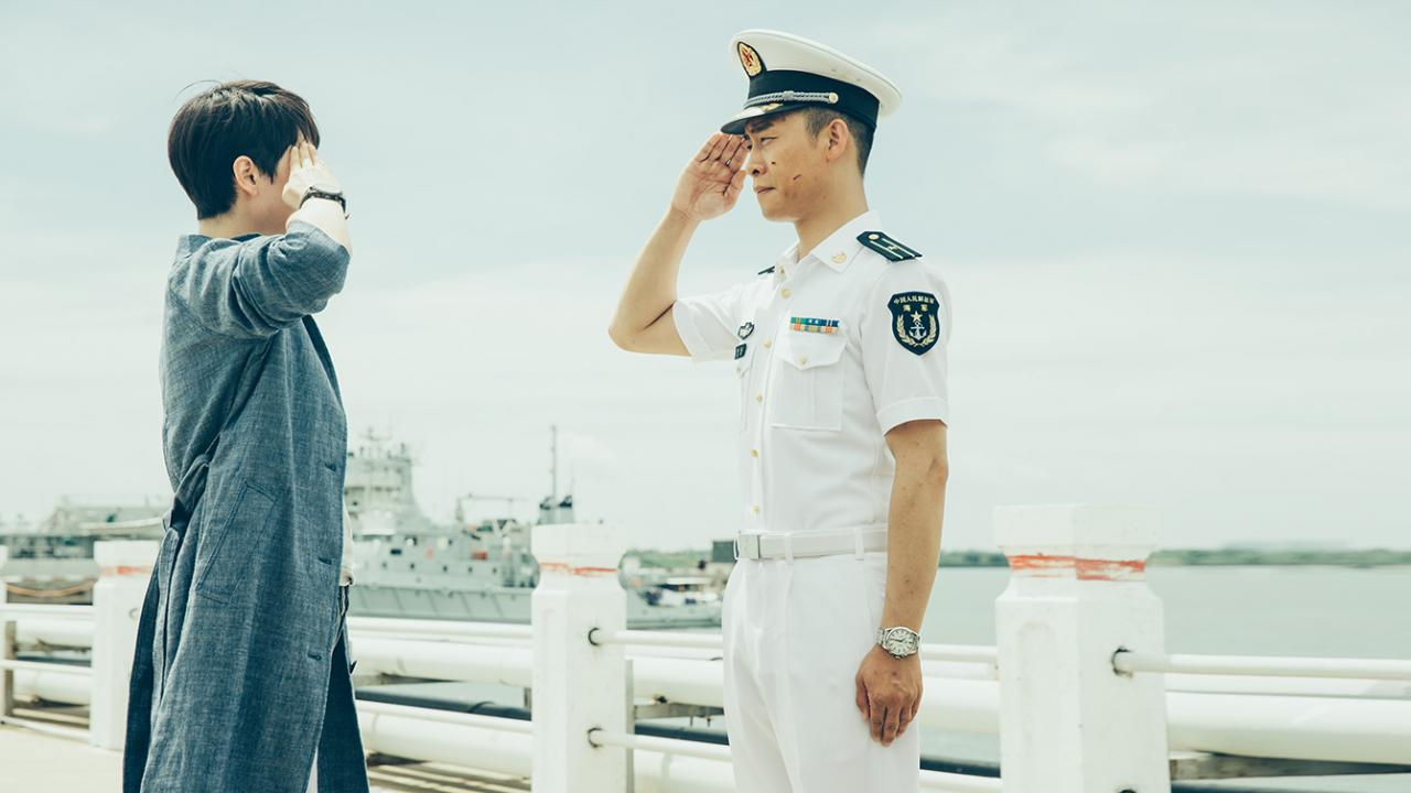 A civilian and military personnel salute one another in OPERATION RED SEA action film