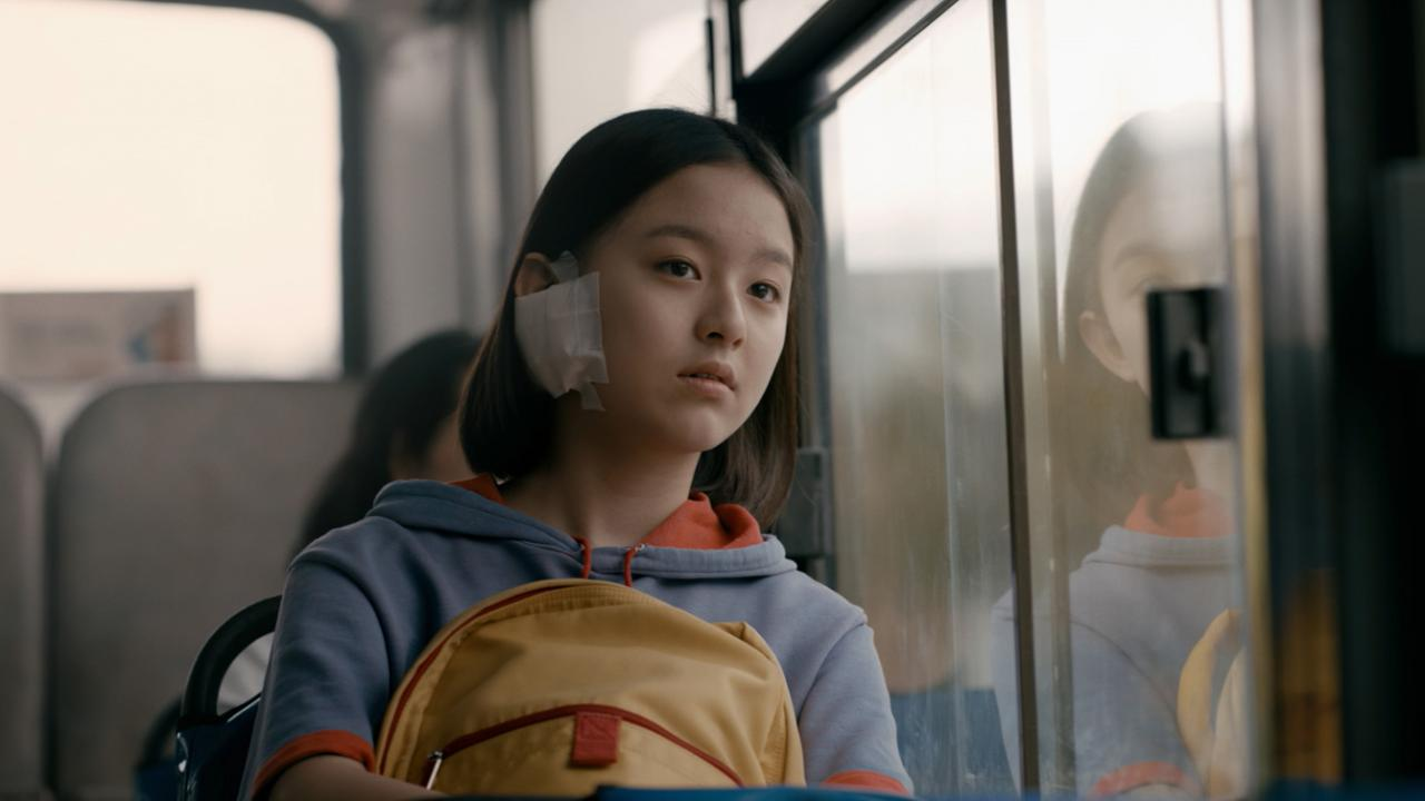 Young adolescent Korean girl looks outside of school bus window