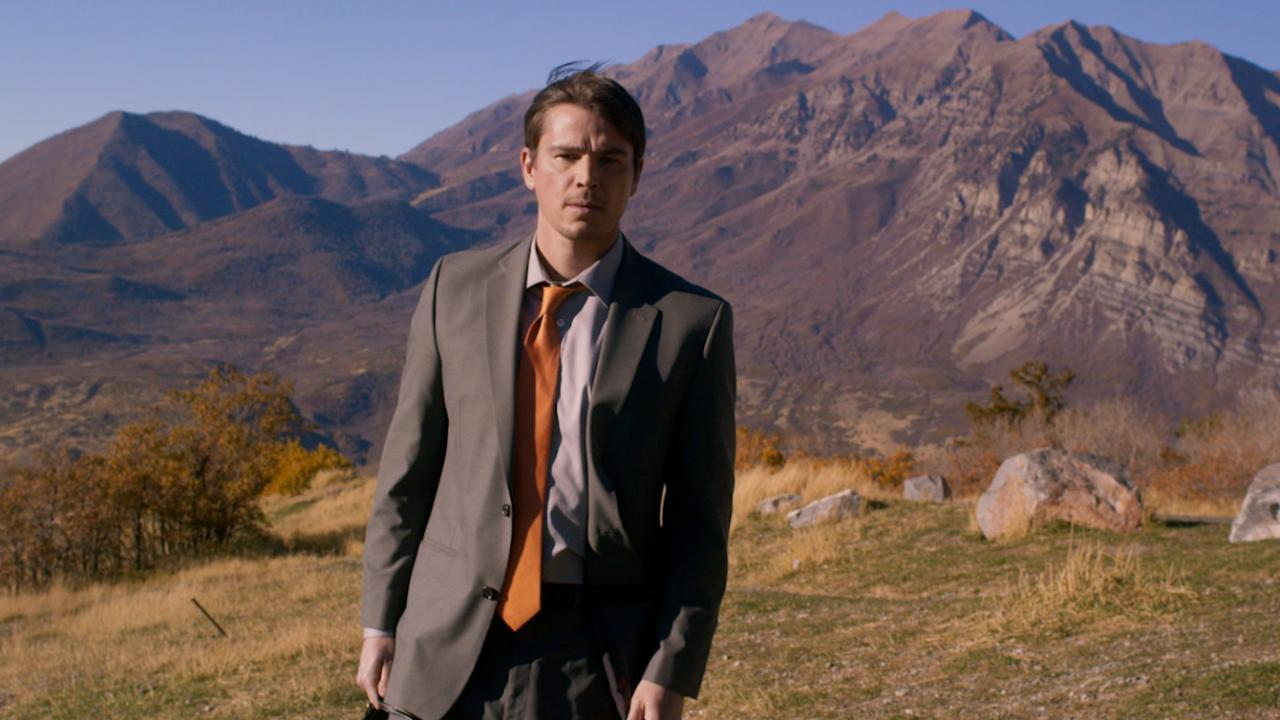 Josh Hartnett pictured in a suit in front of mountain backdrop in VALLEY OF THE GODS
