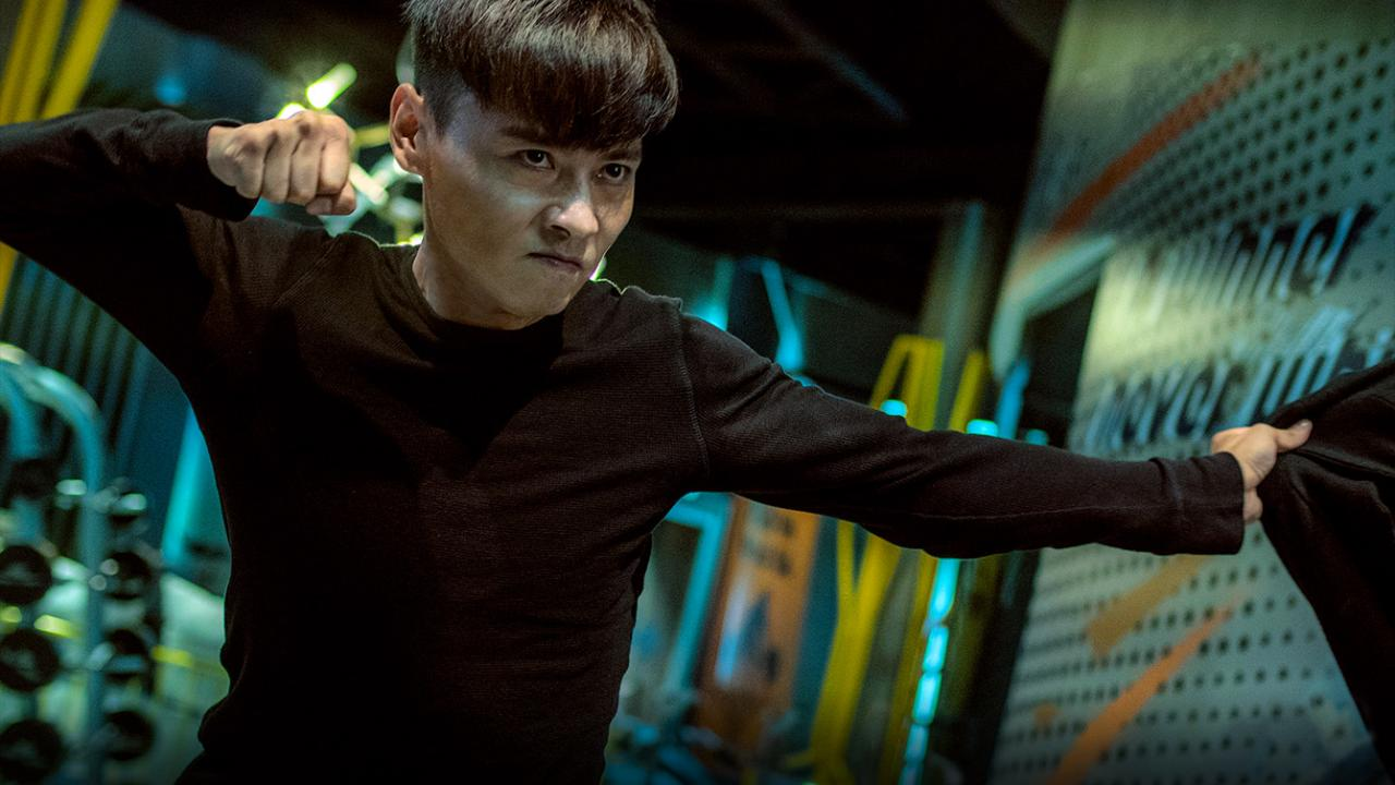Max Jin Zhang in a fighter's stance in INVINCIBLE DRAGON from Well Go USA