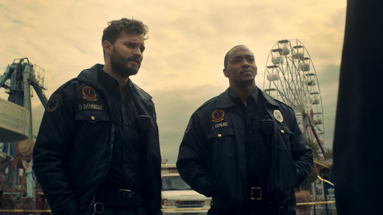 Jamie Dornan and Anthony Mackie standing in a theme park.