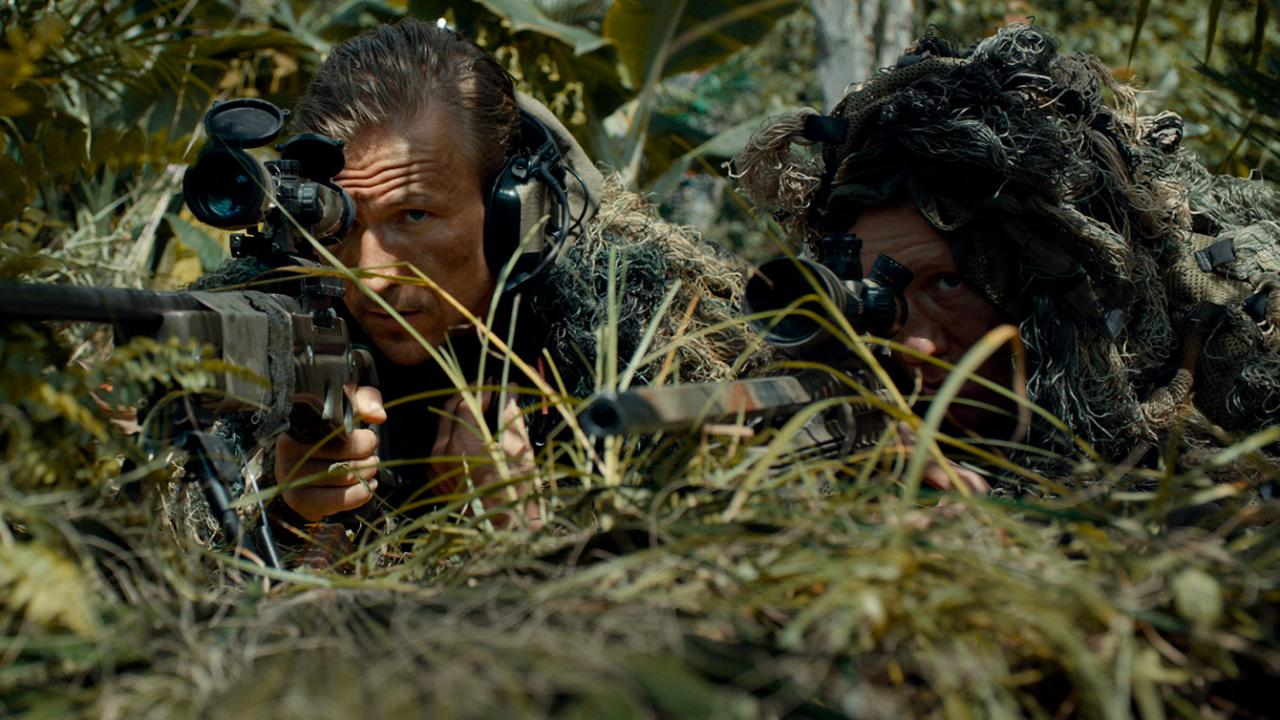 Ivan Kotik as Nikita and a battle buddy taking cover as military snipers in action-thriller RUSSIAN RAID by Well Go USA
