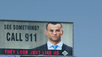 Billboard poster urges passersby to report abormal activity.