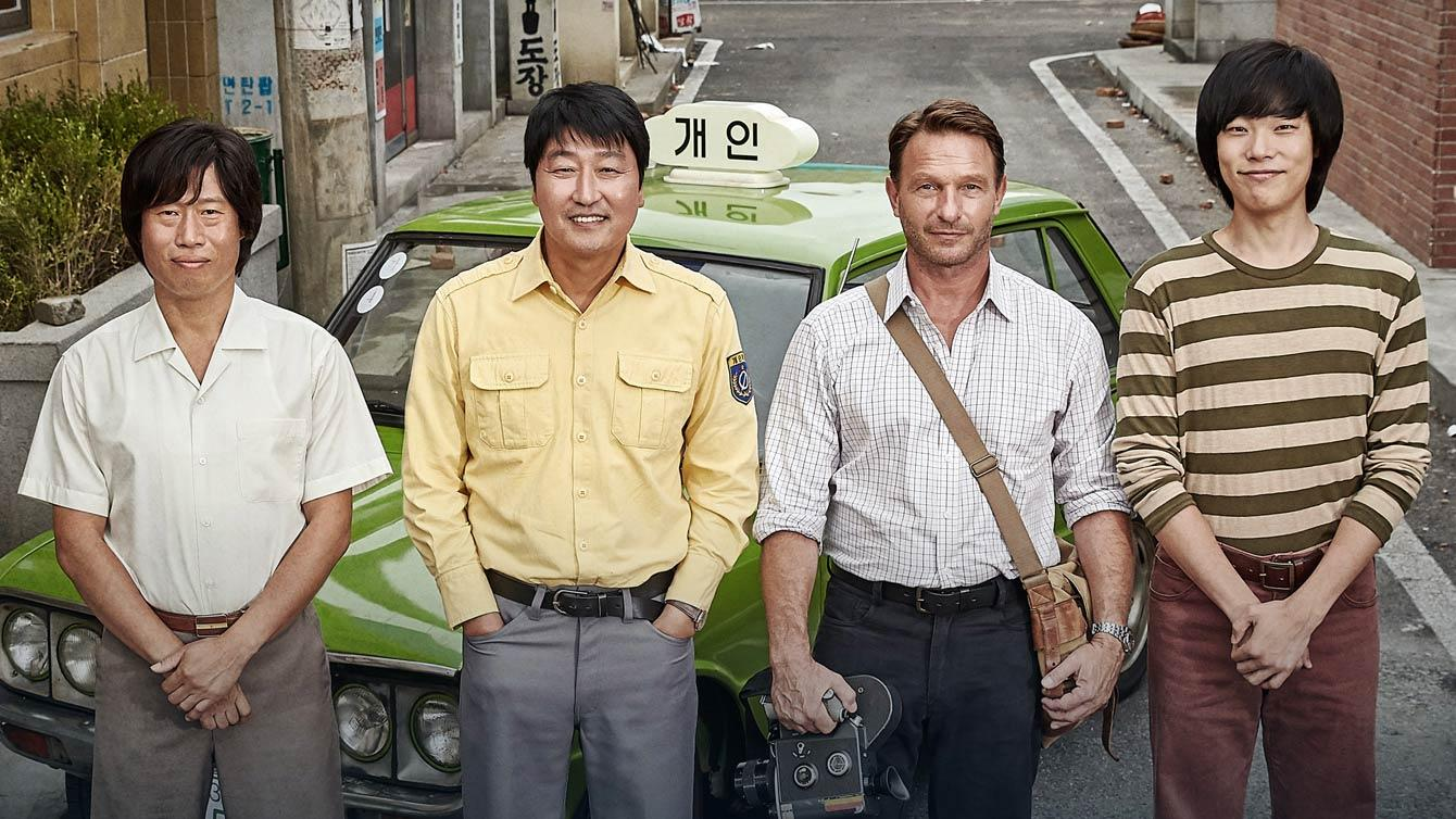 Four men stand by Korean taxi car