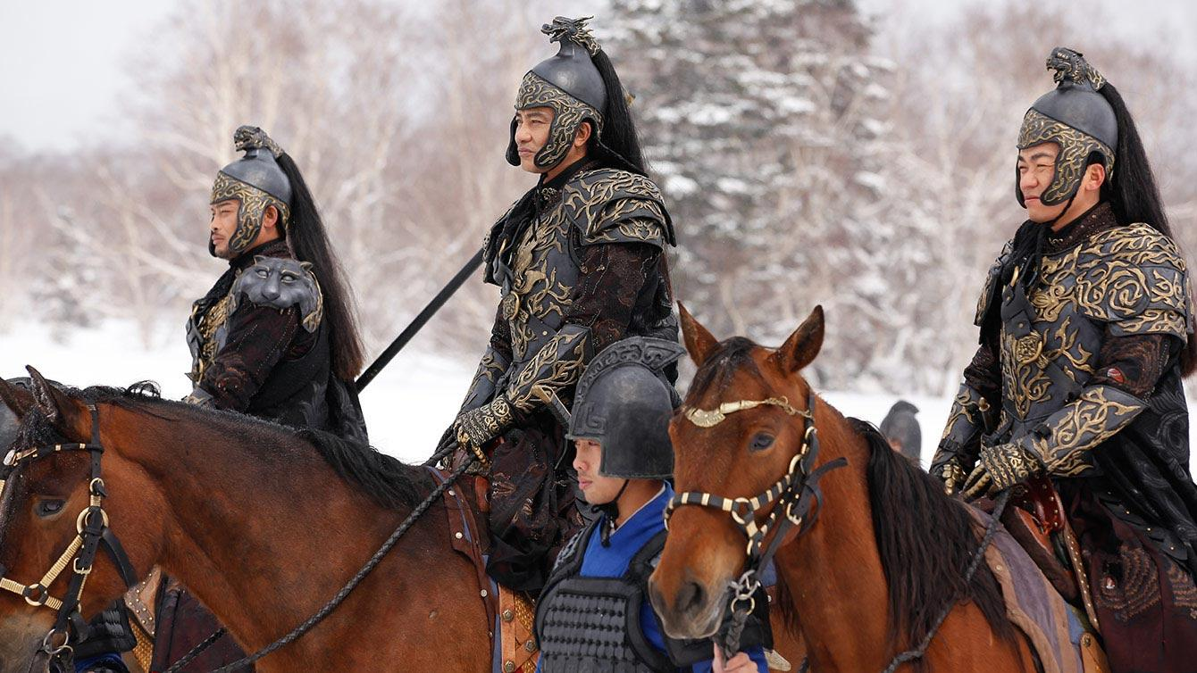 Three guards to the emperor ride horses through the wintery forest in Iceman movie
