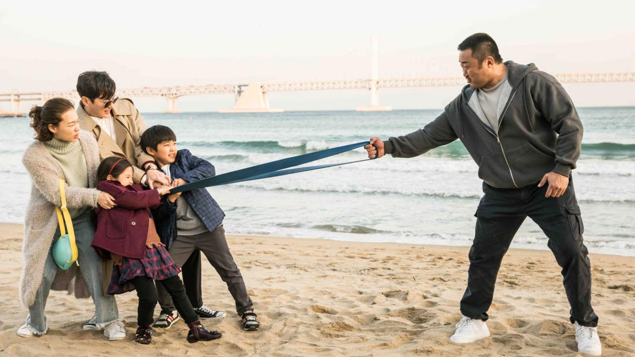 Man, wife and children play in a tug of war on the beach
