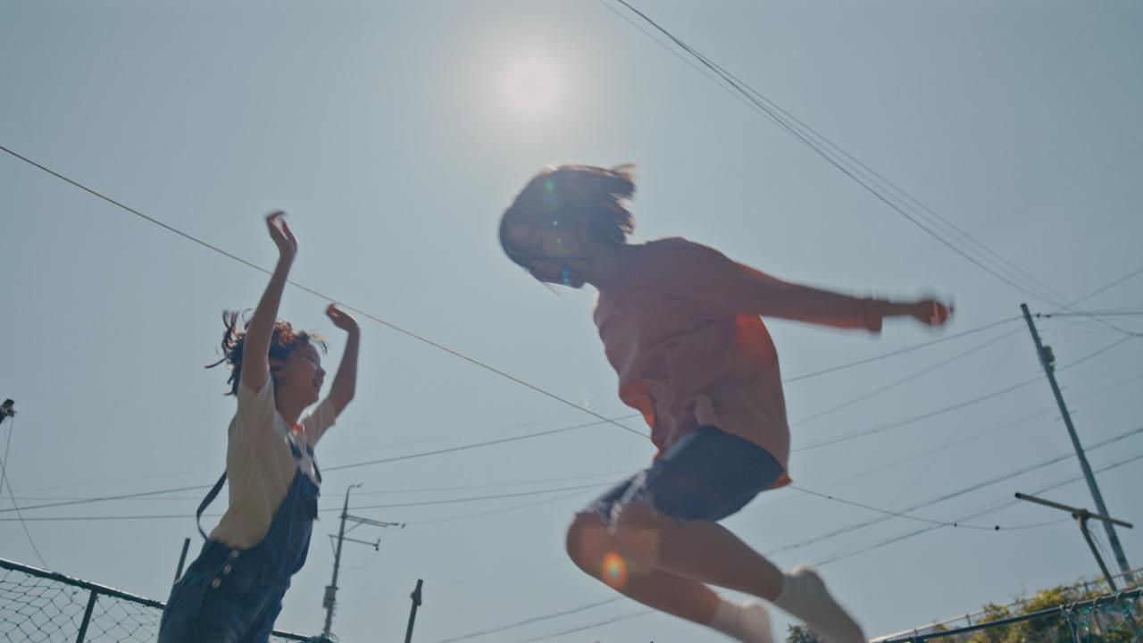 Two young Korean girls play on a trampoline
